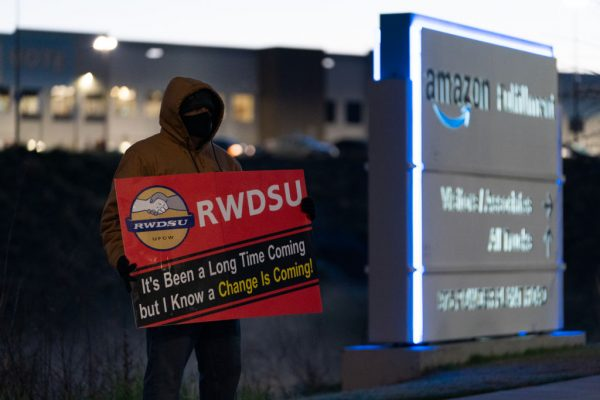An RWDSU union rep holds a sign outside the Amazon fulfillment warehouse at the center of a unionization drive on March 29, 2021 in Bessemer, Alabama. Amazon is giving warehouse staff a raise as it struggles to recruit workers due to socialist welfare policies.