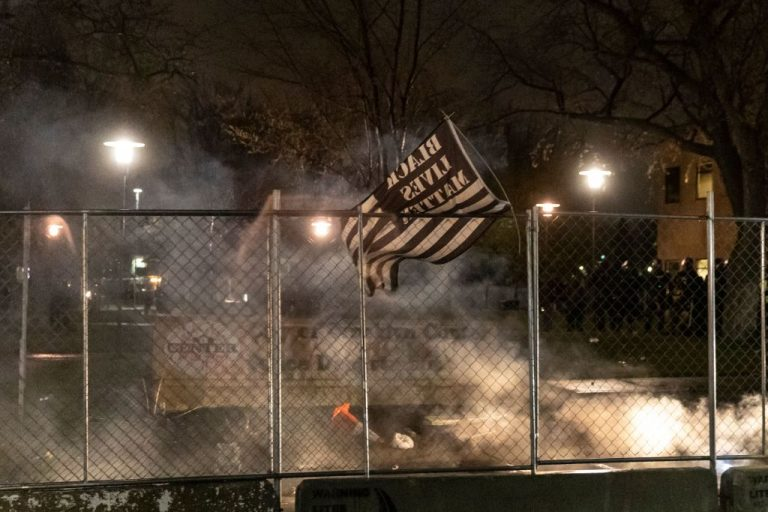 A BLM flag is seen after curfew as demonstrators protest the death of Daunte Wright, who was shot and killed by a police officer in Brooklyn Center, Minnesota on April 12, 2021 after allegedly shooting a teenager in the head.