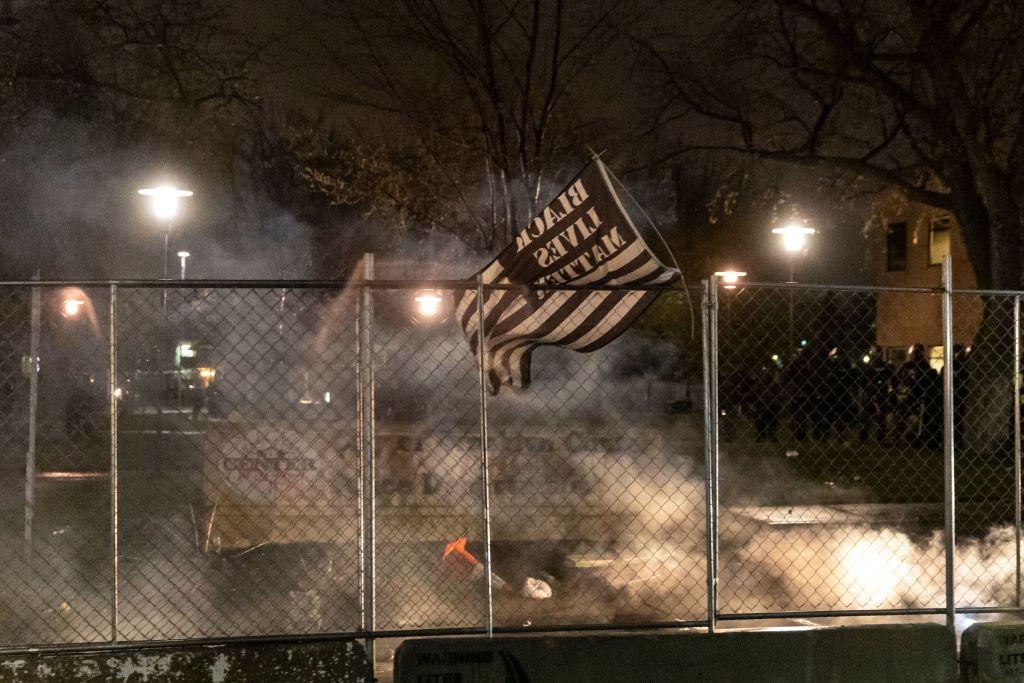 Una bandiera BLM sventola dopo il coprifuoco mentre i manifestanti protestano per la morte di Daunte Wright, che è stato colpito e ucciso da un agente di polizia a Brooklyn Center, Minnesota il 12 aprile 2021 dopo aver presumibilmente sparato alla testa dell'adolescente. (Immagine: KEREM YUCEL/AFP tramite Getty Images)