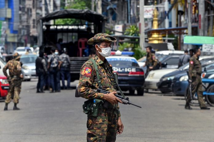 A soldier stands guard along a road as security forces search for protesters, who had been taking part in a demonstration against the military coup, in Yangon on May 7, 2021. A dead poet's wife claims she found the organs missing from her husband's body after it was returned to her by the Tatmadaw.