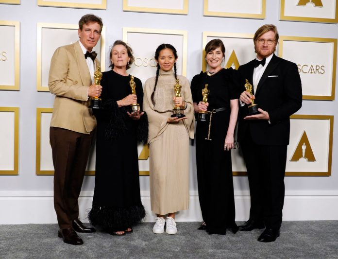 Peter Spears, Frances McDormand, Chloe Zhao, Mollye Asher, and Dan Janvey, winners of Best Picture for Nomadland, pose in the press room at the Oscars on Sunday, April 25, 2021, at Union Station in Los Angeles. Zhao's win has been censored in her home country, ruled by the Chinese Communist Party, because of comments she made in 2013 where she stated China is