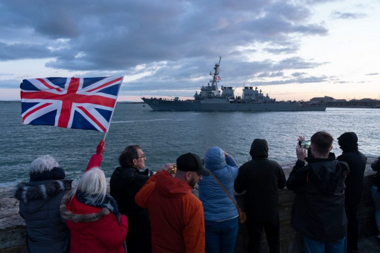 """U.S. warship USS Sullivans leaves Portsmouth Harbour in England at the start of a deployment to the Philippines accompanying the British Aircraft Carrier HMS Queen Elizabeth on May 22, 2021 in Southsea, England. Johnson says England is enforcing the """"law of the sea."""""""