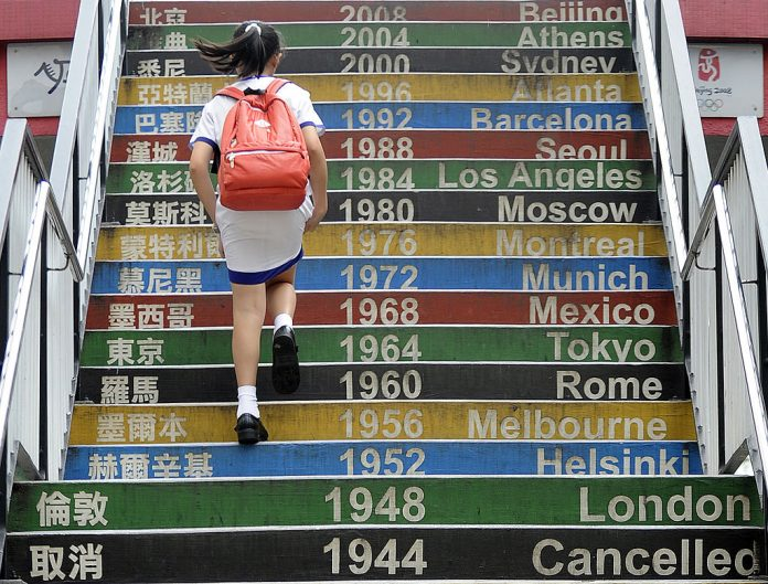 A student walks up stairs decorated with past Olympic dates in Hong Kong on June 13, 2012. SOAS University, formerly the School of Oriental and African Studies, has warned faculty members to protect students during classes on Chinese Communist Party-sensitive subjects fearing they can be arrested when entering Hong Kong or China for attending classes.