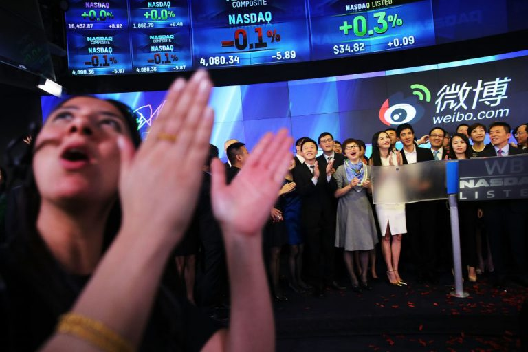 People cheer as China's Weibo began trading on Nasdaq on April 17, 2014 in New York City. An investigation by Oxford and Associated Press discovered an army of fake accounts on Facebook and Twitter help promote Chinese Communist Party media and officials. Big Tech fails to deal with the CCP with the same strict standards it dealt with Donald Trump and U.S. conservatives.