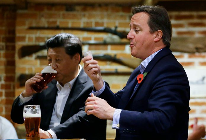Ex-British Prime Minister David Cameron gets out money to pay for drinks as China's President Xi Jinping drinks a pint of beer during a visit to the The Plough pub on October 22, 2015 in Princes Risborough, England. The Plough's owner, Greene King, is now in the hands of Hong Kong billionaire Li Ka Shing as part of an unhealthy trend of British businesses selling out to the Communist Party.