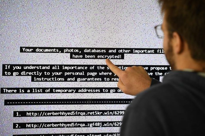 An IT researcher shows on a giant screen a computer infected by ransomware at the LHS (High Security Laboratory) of the INRIA (National Institute for Research in Computer Science and Automation) in Rennes, France on November 3, 2016. Ransomware attacks on high value U.S. targets is becoming increasingly more common according to cybersecurity analysts.