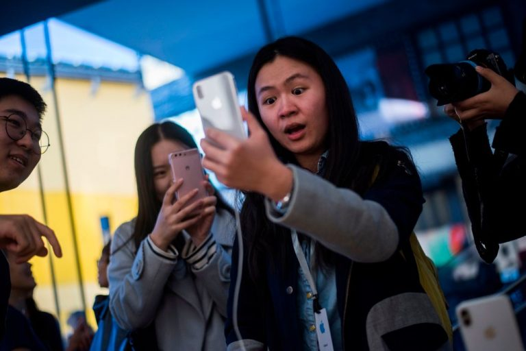 A Chinese woman reacts while setting up the facial recognition feature on her iPhone X inside an Apple showroom in Beijing on November 3, 2017. A report found Apple, along with several other members of the Big Tech cartel, heavily relies on suppliers who utilize a Chinese Communist Party forced labor scheme exploiting Uyghur Muslims.