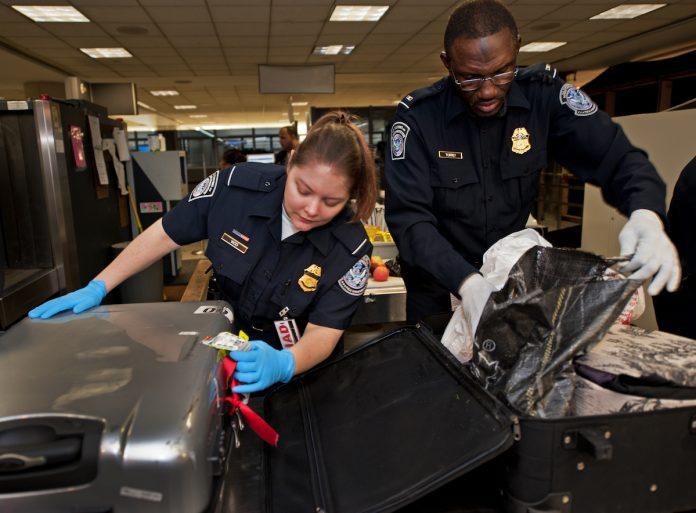 Gli ufficiali della US Customs and Border Protection Officer  aprono i bagagli dei viaggiatori aerei internazionali presso l'area doganale e di immigrazione degli Stati Uniti all'Aeroporto Internazionale di Dulles (IAD) il 21 dicembre 2011 a Sterling, Virginia, vicino Washington DC. (Immagine: PAUL J. RICHARDS/AFP tramite Getty Images)