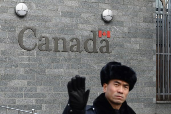 A guard attempts to block photos from being taken outside the Canadian Embassy in Beijing on January 27, 2019. A virologic scandal involving a Canadian researcher with ties to communist China boiled over after she and her husband were removed from Winnipeg's National Microbiology Laboratory by the RCMP.
