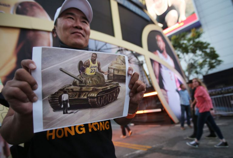 A pro-Hong Kong activist holds an image depicting LeBron James aboard a Chinese tank in Tiananmen Square before the Los Angeles Lakers season opening game against the LA Clippers outside Staples Center on October 22, 2019 in Los Angeles, California. James will evade punishment for dodging league COVID-19 protocols to attend a promotional event for a tequila brand he is invested in.