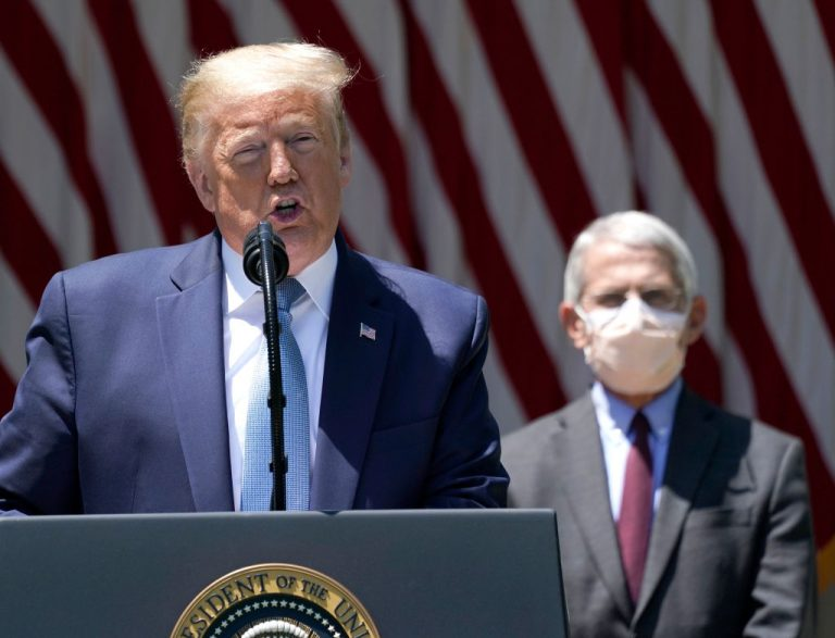 Former president Donald Trump is flanked by Dr. Anthony Fauci, director of the National Institute of Allergy and Infectious Diseases while speaking about coronavirus vaccine development in the Rose Garden of the White House on May 15, 2020 in Washington, DC. Trump has asked China to pay 10 trillion dollars as compensation for the economic damages and lives lost from the COVID-19 pandemic.