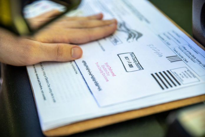 Democrats in the House recently blocked Republican efforts to pass an election reform bill. A voter's ballot is shown being stamped by a poll worker before getting sent to a ballot drop off location on October 13, 2020 in Austin, Texas.