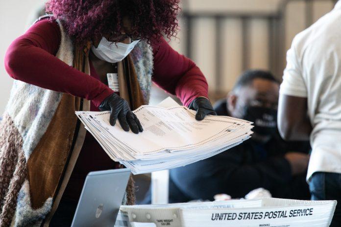 Un lavoratore della contea di Fulton sposta una pila di schede elettorali per assenza alla State Farm Arena il 6 novembre 2020 ad Atlanta, Georgia. (Immagine: Jessica McGowan tramite Getty Images)