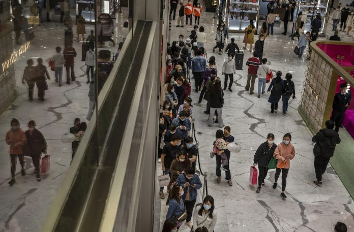 """China's economic growth is being threatened by a new """"lying flat"""" movement among young citizens. Shoppers wait in line outside a Chanel store at a mall on April 18, 2021 in Beijing, China."""