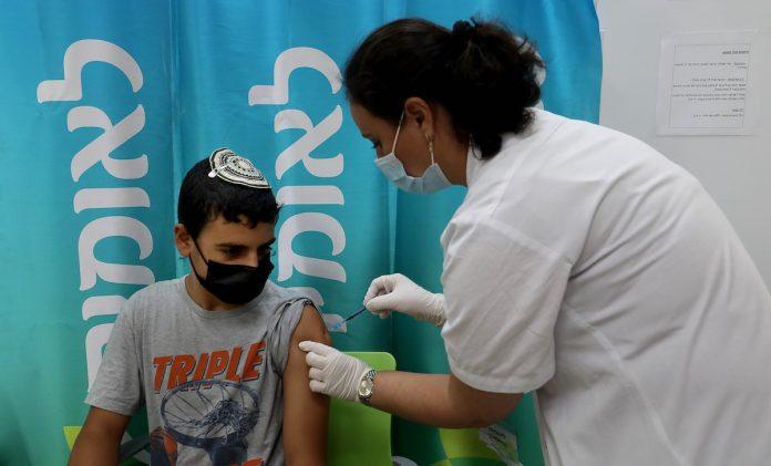 Un operatore sanitario somministra il vaccino COVID-19 a un ragazzo in un centro di servizi sanitari nella città israeliana centrale di Modiin, il 22 giugno 2021. Martedì il Ministero della Salute israeliano ha segnalato 139 nuovi casi di COVID-19,  per un numero totale nel paese pari a 840.079 casi. (Immagine: Gil Cohen Magen/Xinhua tramite Getty Images)