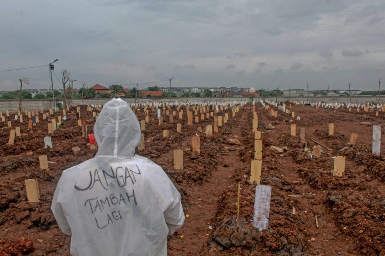 Funeral workers are seen standing in front of rows of graves from deaths associated with Covid-19 at a special cemetery in Jakarta, Indonesia on June 24, 2021. Countries who have relied on the Chinese Communist Party's vaccine diplomacy offerings are still suffering major case counts.