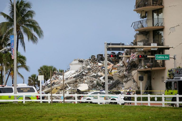 Police cars parked in front of the debris from a partially collapsed building in Surfside north of Miami Beach, on June 24, 2021. Search and rescue teams are continuing to look for people in the rubble.