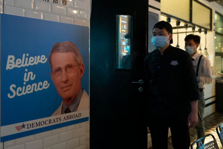 A poster of Anthony Fauci is seen as members of Democrats Abroad in Shanghai celebrate as Joe Biden is sworn in as 46th President of the United States at a bar on January 21, 2021 in Shanghai, China. Jack Posobiec says the Biden White House is looking to break up with Fauci after exposure to his emails via FOIA requests from Washington Post and BuzzFeed left the NIAID Director looking exposed.