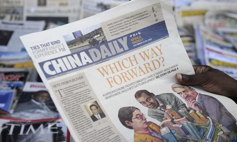 China is spending millions to publish pro-communist content through U.S. media outlets. In the image, a newspaper consumer reads a copy of China's Africa edition of its daily newspaper in front of a news stand in the Kenyan capital on December 14, 2012.