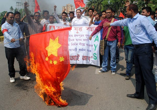 Activists of the Asom Yuva Santha (AYS) burn a CCP flag during a protest in Guwahati on March 25, 2013, against the proposed construction of dams on the middle reaches of the River Brahmaputra in China, part of a water project. In 2021, the CCP plans to build a dam that will generate hydropower three times the size of the notorious Three Gorges .
