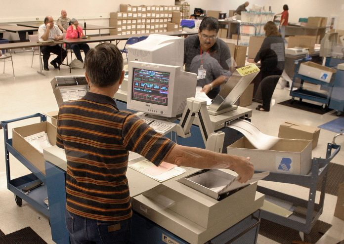 Three Republican lawmakers from Pennsylvania will soon meet up with Arizona legislators and travel to the Maricopa County audit site. Pictured are election workers using ballot tabulation machines to count early ballots at the Maricopa County Tabulation and Election Center in October 2004 in Phoenix, Arizona.