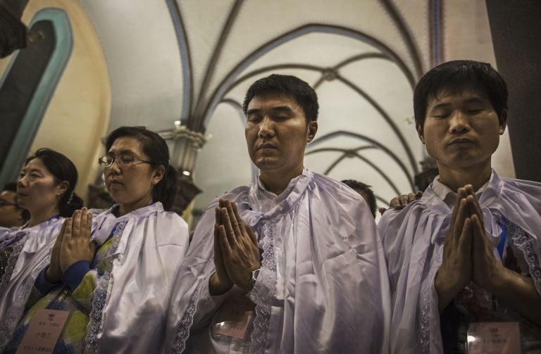 Newly baptized Chinese Catholic worshippers pray during a special ceremony at a mass on Holy Saturday during Easter celebrations at the government sanctioned West Beijing Catholic Church on April 15, 2017 in Beijing, China. China, an officially atheist country, places a number of restrictions on Christians, allowing legal practice of the faith only at state-approved churches. (Image: Kevin Frayer via Getty Images)