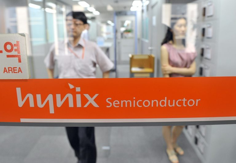 The U.S. recently announced increased cooperation with South Korea in fields such as semiconductors, AI, and 6G. Employees of Hynix Semiconductor are shown walking past the company's logo at a branch in Seoul on July 21, 2011. Hynix Semiconductor is the world's second-largest memory chip maker.