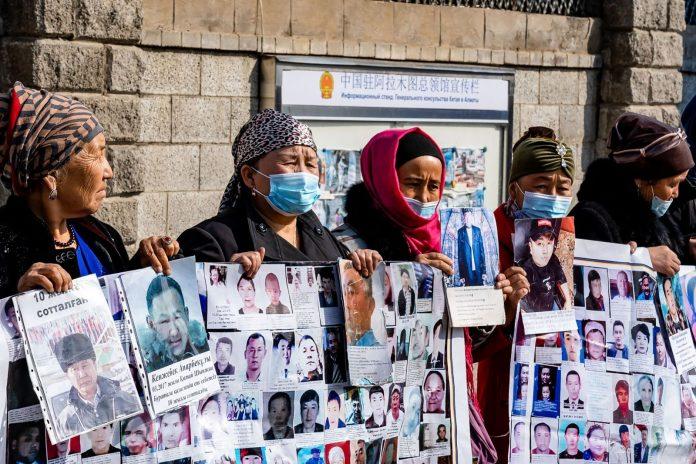 il 9 marzo 2021 Gulnur Kosdaulet (seconda a sinistra), 48 anni, protesta contro la detenzione di suo marito in Cina. Si trova fuori dal consolato cinese nella più grande città del Kazakistan, Almaty, il 9 marzo 2021. Gulnur Kosdaulet e un gruppo di dimostranti per lo più donne organizzano picchetti quotidiani del consolato per chiedere il rientro sicuro a casa per i loro parenti , che sono scomparsi, imprigionati o intrappolati nella repressione cinese delle minoranze nella regione dell'estremo Xinjiang. (Immagine: ABDUAZIZ MADYAROV/AFP tramite Getty Images)