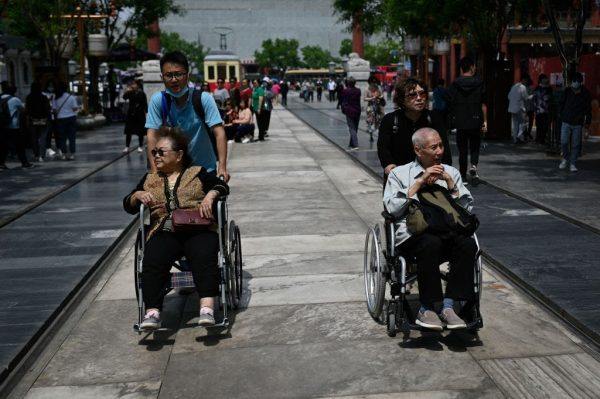 An elderly man and woman are pushed in wheelchairs along a street in Beijing on May 11, 2021. The CCP, facing compounding crises of a collapsing birth rate and an increasingly elderly population, has resorted to upgrading its two-child policy to a 3-child policy.