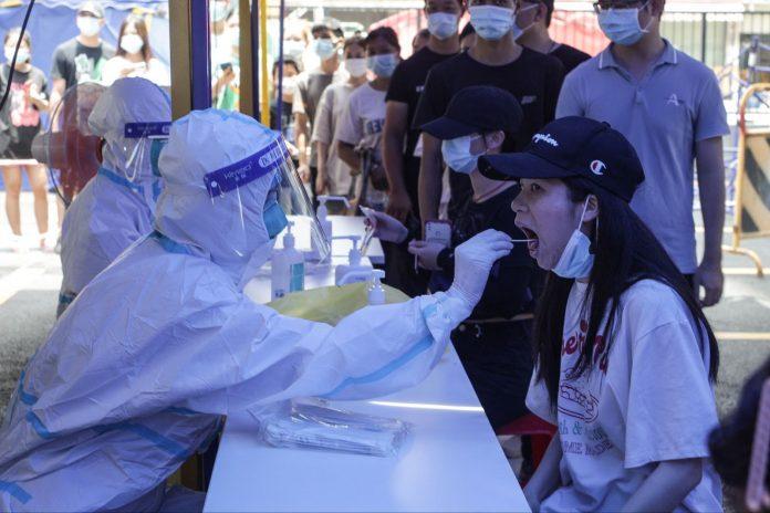 Questa foto scattata il 30 maggio 2021 mostra una donna che riceve un test dell'acido nucleico per il coronavirus Covid-19 a Guangzhou, nella provincia meridionale del Guangdong in Cina. (Immagine: STR/AFP tramite Getty Images)
