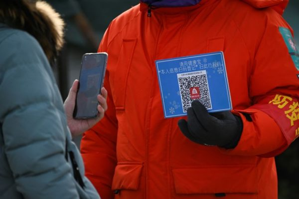 A woman uses her mobile phone to scan a QR code for health registration before being allowed to enter an outdoor ice rink in Beijing on January 12, 2021.