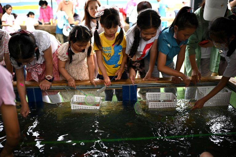 Chinese-kids-play-with-fish-China-population-decline
