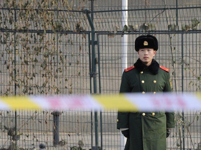 Un ufficiale della polizia paramilitare cinese fa la guardia accanto a un poliziotto che controlla la scena davanti all'ambasciata nordcoreana a Pechino il 20 dicembre 2011. (Immagine: LIU JIN/AFP tramite Getty Images)