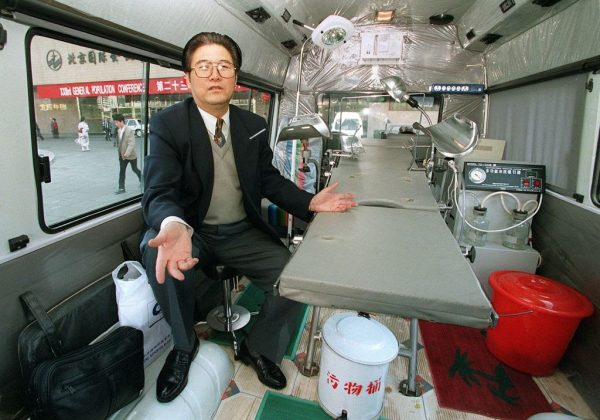 Zhou Zhengxiang sits in the surgeon's seat as he explains the medical features of his mobile abortion, sterilization and birthing van created by his company, the China Triple-U High Technology Industrial Group, outside the General Population Conference in Beijing. Due to the one-child policy, 336 million abortions were recorded between 1971 and 2013.