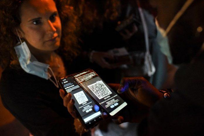 Il 10 luglio 2021 un membro del personale di sicurezza controlla il pass sanitario di un cliente all'ingresso di una discoteca a Saint-Jean-de-Monts, nella Francia occidentale. (Immagine: SEBASTIEN SALOM-GOMIS/AFP tramite Getty Images)