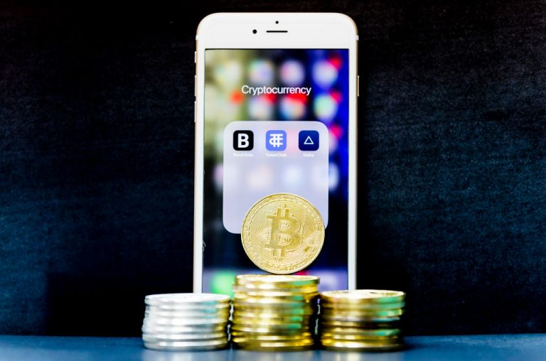 A visual representation of the digital Cryptocurrency, Bitcoin, and a smartphone with the icons for the Cryptocurrency related apps from Blockfolio, TokenClub, and Delta are seen on the screen on September 4, 2018 in Hong Kong.
