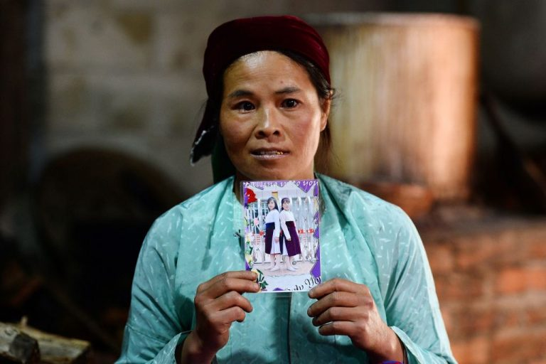 This picture taken on October 27, 2018 shows Ly Thi My, a Vietnamese mother posing with a photograph of her missing daughter Di at her house in Meo Vac, a mountainous border district between Vietnam's Ha Giang province and China. Di is suspected to have crossed into China. The State Department's annual Trafficking in Persons report found the CCP was one of 11 countries who had a government policy of engaging in human trafficking for the purposes of forced labor and sexual slavery.