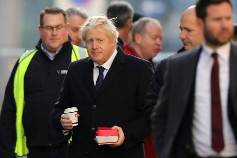 British Prime Minister Boris Johnson visits the scene of the London Bridge stabbing attack on November 30, 2019 in London, England with fast food in hand. Johnson's regime announced plans to begin monitoring UK family eating habits and exercise activity with a pilot program alarmingly similar to China's social credit. Johnson is piggybacking on COVID-19, saying anti-obesity efforts will reduce deaths and serious illness from the disease.