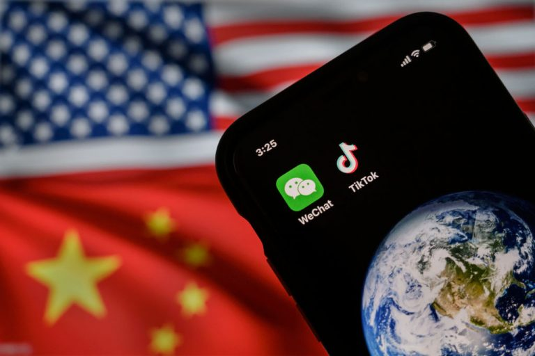 In this photo illustration, a mobile phone can be seen displaying the logos for Chinese apps WeChat and TikTok in front of a monitor showing the flags of the United States and China on an internet page, on September 22, 2020 in Beijing, China. A recent investigation by Wall Street Journal found TikTok's algorithm can learn its users' desires in as little as 40 minutes and will quickly bury the account in a rabbit hole of related content.