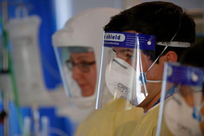 Il pompiere Matt Smither con addosso una visiera aiuta un paziente colpito da COVID-19 mentre lavora a fianco degli infermieri di terapia intensiva nell'Unità di terapia intensiva (ICU) presso il Queen Alexandra Hospital di Portsmouth, nel sud dell'Inghilterra, il 23 marzo 2021. (Immagine: ADRIAN DENNIS/AFP tramite Getty Images)