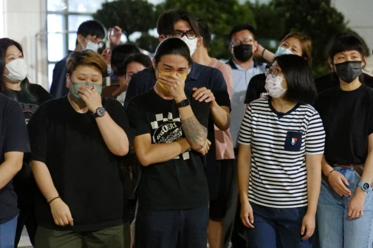 Apple Daily journalists get emotional after thanking supporters gathered outside their office in Hong Kong early on June 24, 2021, as the pro-democracy tabloid was forced to close after 26 years under a sweeping new national security law.