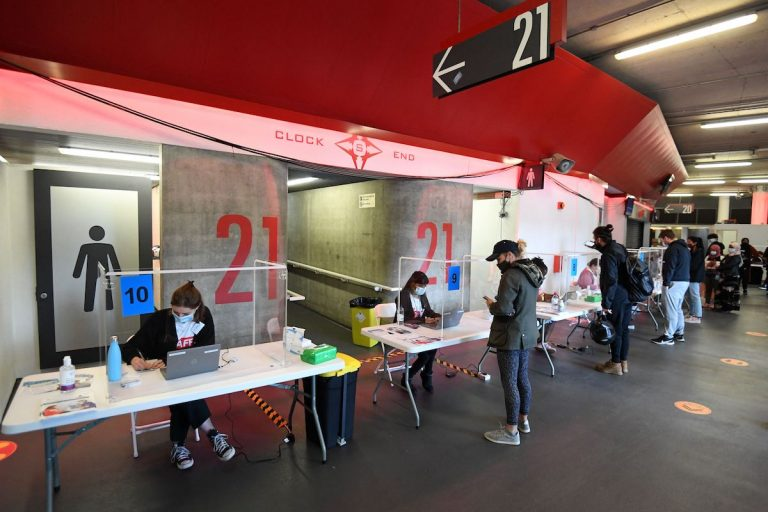 Members of the public arrive to receive a dose of a COVID-19 vaccine inside a temporary vaccination centre set up at the Emirates Stadium, home to Arsenal football club, in north London on June 25, 2021.