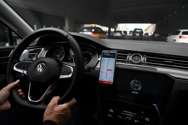 A driver uses the map on the Didi Chuxing ride-hailing app on his smartphone while driving on a street in Beijing on July 5, 2021. The Communist Party put the brakes on the app just days after its debut on the NYSE.