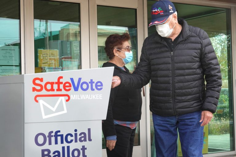 Residents drop mail-in ballots in an official ballot box outside of the Tippecanoe branch library on October 20, 2020 in Milwaukee, Wisconsin.
