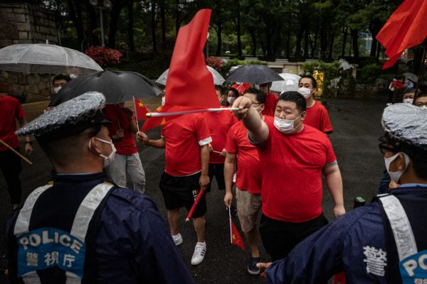 Japanese police officers stand in front of paid Chinese Communist Party supporters at Shinjuku Central Park on July 1, 2021 in Tokyo, Japan. Xi Jinping is still holding on to an illusion that his Communist Party can maintain power despite all the scandals and debts it has incurred over the course of the last 100 years.