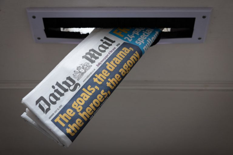 """A photo illustration showing a copy of the Daily Mail newspaper in a letterbox on July 12, 2021 in London, England. Editor for the Australia branch of the publication, Barclay Crawford, in a leaked video of a conference call instructed staff to """"call out the 'anti-vaxx weirdos'"""" and to forgo journalistic standards in favor of serving as an establishment narrative propaganda outlet by """"rubbishing their ridiculous claims."""""""