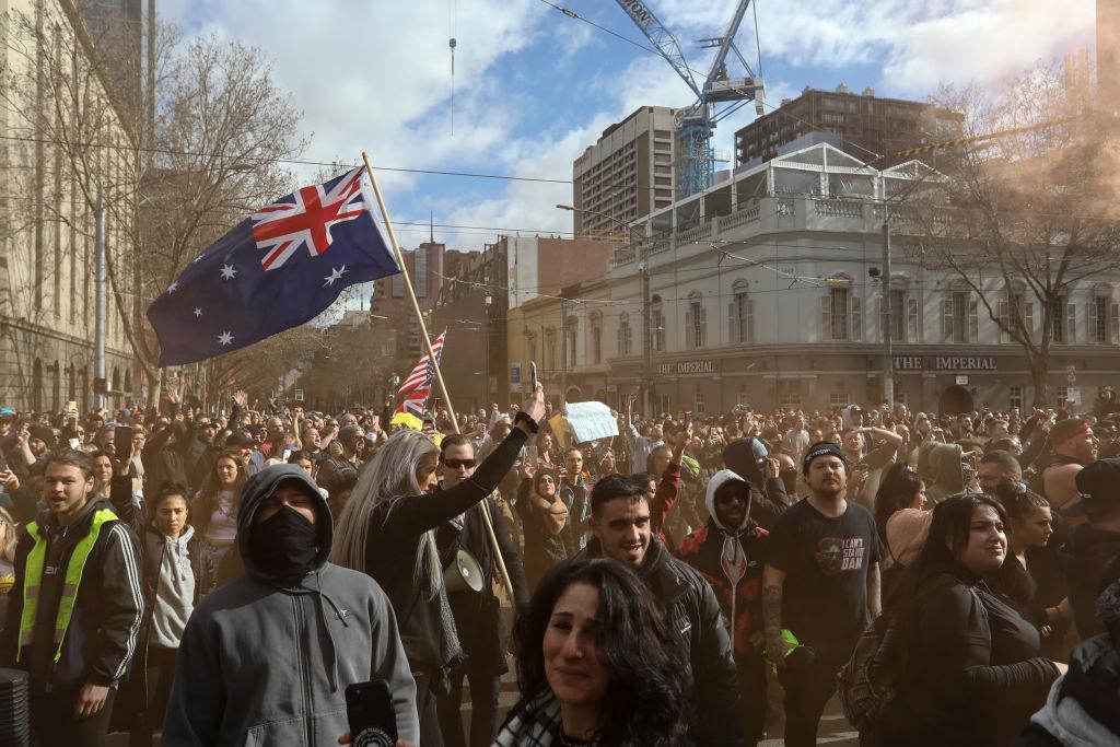 I manifestanti si radunano davanti al Parlamento durante una manifestazione anti-blocco il 24 luglio 2021 a Melbourne, in Australia. La polizia australiana ha incoraggiato i cittadini a denunciarsi a vicenda e ha promesso di utilizzare tutti i filmati di sorveglianza disponibili per punire coloro che hanno partecipato agli eventi. (Immagine: Diego Fedele/Getty Images)
