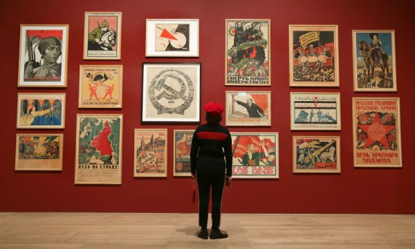An individual takes in early 1900's socialist and communist propaganda from Adolf Strakhov and Valentin Shcherbakov during an exhibition allowed to be held at Tate Modern in London on November 7, 2017. Two thirds of the UK's U45 population want to live under socialism after being educated by media rhetoric, found a recent study.