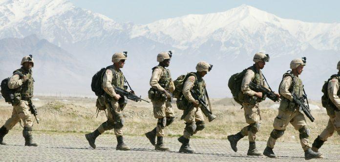 I soldati della decima divisione da montagna dell'esercito americano camminano sull'asfalto mentre si preparano a entrare in un elicottero Chinook il 13 marzo 2002 presso la base aerea di Bagram vicino a Kabul, in Afghanistan. (Immagine: Joe Raedle/Getty Images)