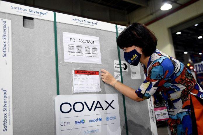Un funzionario del Ministero della Salute controlla i documenti su un container che trasporta la prima spedizione delle dosi di vaccino Covid-19 AstraZeneca/Oxford, nell'ambito del programma COVAX dell'OMS, mentre arriva al terminal cargo dell'aeroporto internazionale di Noi Bai ad Hanoi il 1 aprile 2021. Il 12 luglio COVAX ha acquistato 110 milioni di dosi di vaccini made in China per la distribuzione internazionale. (Immagine: NHAC NGUYEN/AFP tramite Getty Images)